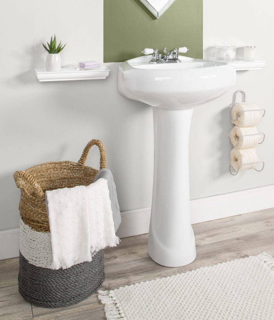 A low view of bathroom showing decorative items: basket holding towels, plant on shelf, toilet paper holder showing rolls wrapped in organic decorative paper.