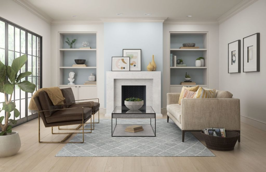 A modern living room featuring white walls painted in white color called Painter's White.  The room is accented with a light blue paint color called Light Drizzled which is being featured in the fireplace wall and two bookshelves.  The overall feel of the room is modern yet cozy and welcoming.