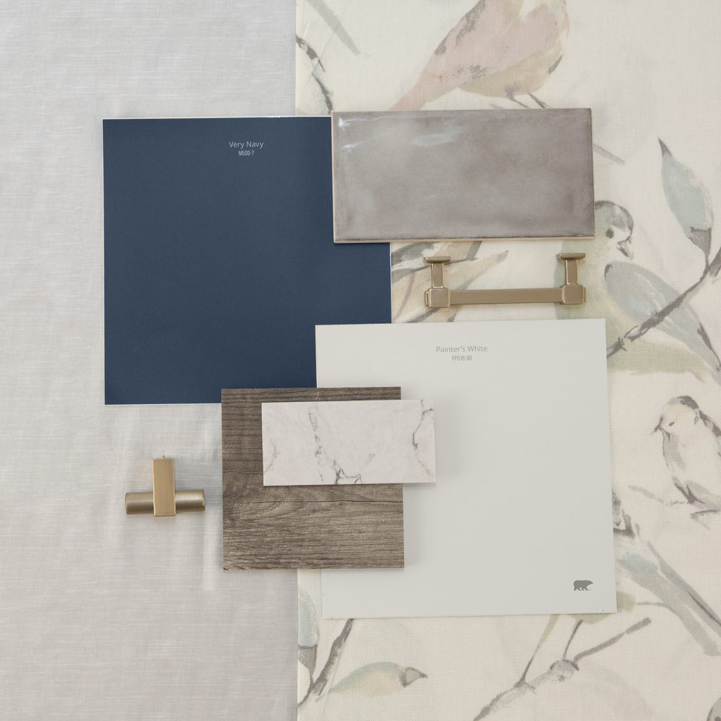 This is an inspirational photo on how to furnish your kitchen. There are two peel n stick swatches in Very Navy and Painter's White. These are paired with dark wood swatch for flooring, white granite swatch, and a light gray tile backsplash, there is also a knob for cabinets and a handle for cabinets, each are in a chrome tone.  Behind the materials is fabric laid out in a very light gray tone and other fabric has pastel colored birds sitting on branches.