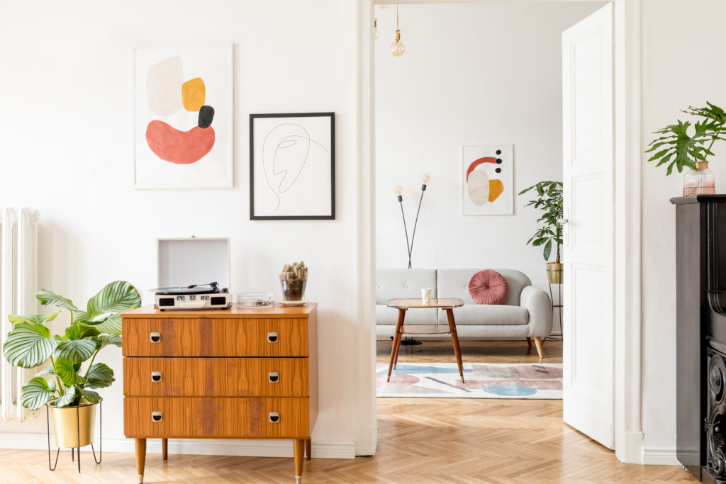 An open mid-century living space and hallway.  The rooms feature walls painted in white color called Painter's White.  The walls are decorated with abstract art. There are plants and other greenery on this living space.