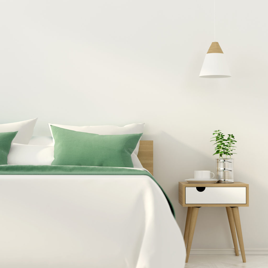 A scandi-modern bedroom featuring a white wall painted in white color called Painter's White. There blonder wood and white laminate side table and the bed is dressed in simple white and Kelly-green bedding.