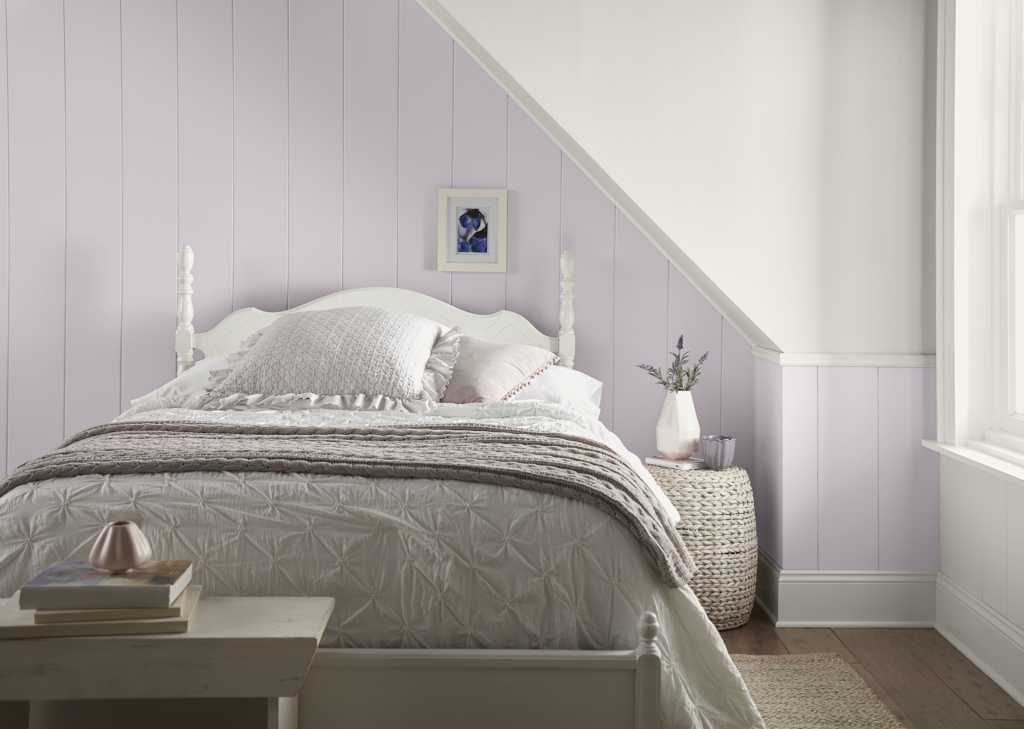 A relaxing bedroom featuring a paneled wall painted in light purple color called Dusty Lilac.   There is a sloping architectural detail which create visual interest.  Sloping detail, trim and wooden bed are painted in white color.