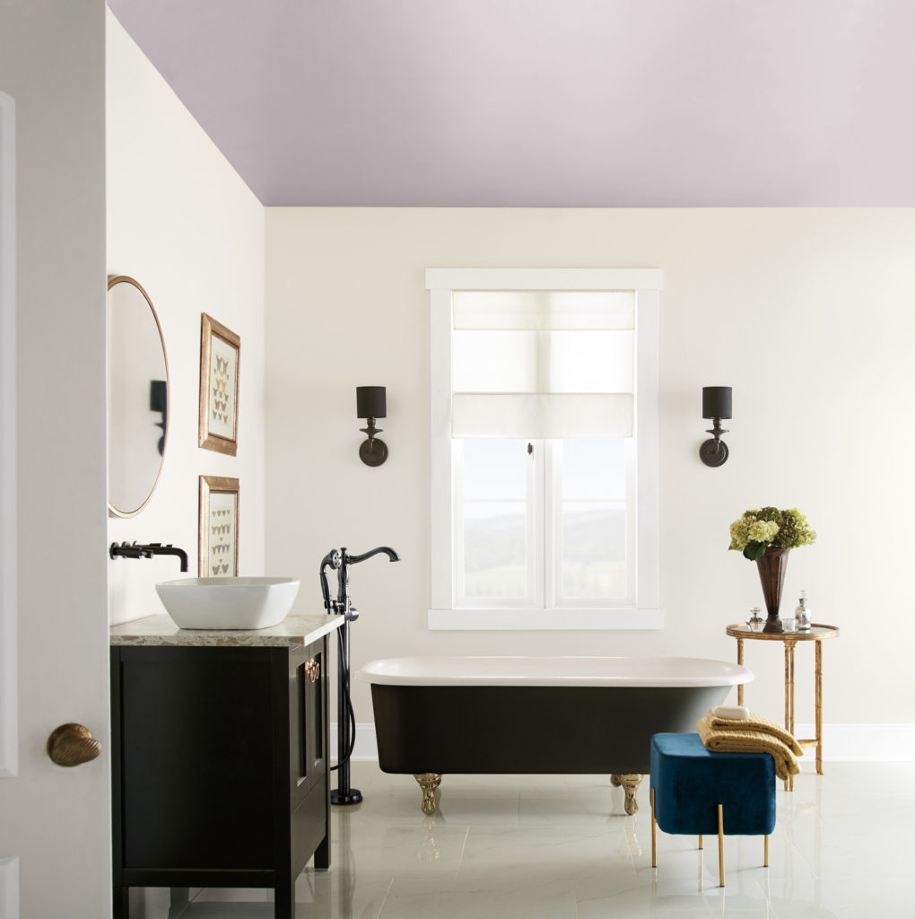 A bathroom featuring a ceiling painted in a soft purple color called Dusty Lilac.  The bathroom is decorated with black claw-foot tub, hardware and furniture.