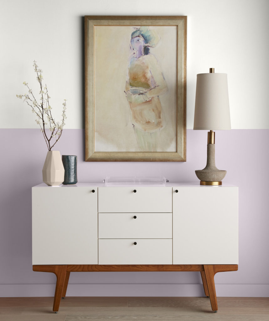 A two tone wall featuring with a mid-century modern console.  The upper wall is painted in a white color called Painter's White, the lower wall is painted in light purple color called Dusty Lilac.