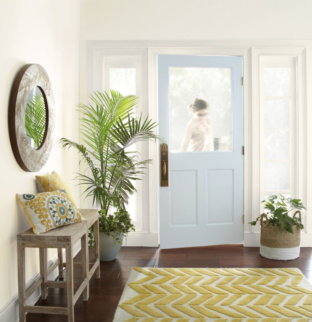A casual entry-foyer featuring white walls painted in color called Painter's White.  The door is painted in a light pastel blue called Light Drizzle. The room is also accented with decorative pillow and rug with pops of mustard yellow.