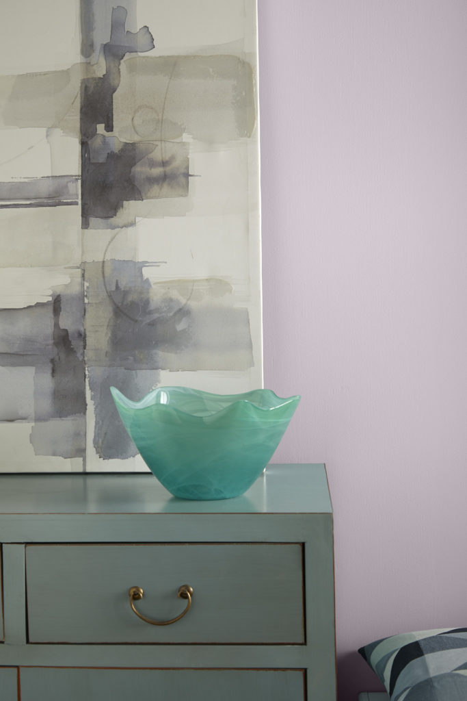 A close detail of a interior room setting decorated with an aqua colored furniture piece and watercolor artwork on the wall. The room is painted in light purple color called Dusty Lilac.