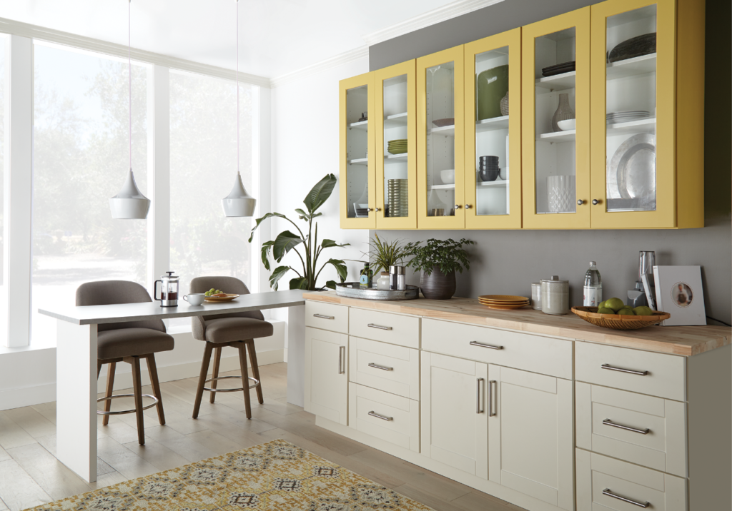 A casual modern kitchenette -breakfast nook featuring white and gray walls.  The kitchenettes upper cabinets are painted in cheery yellow called Charismatic. The lower cabinets are painted in white color called Painter's White.