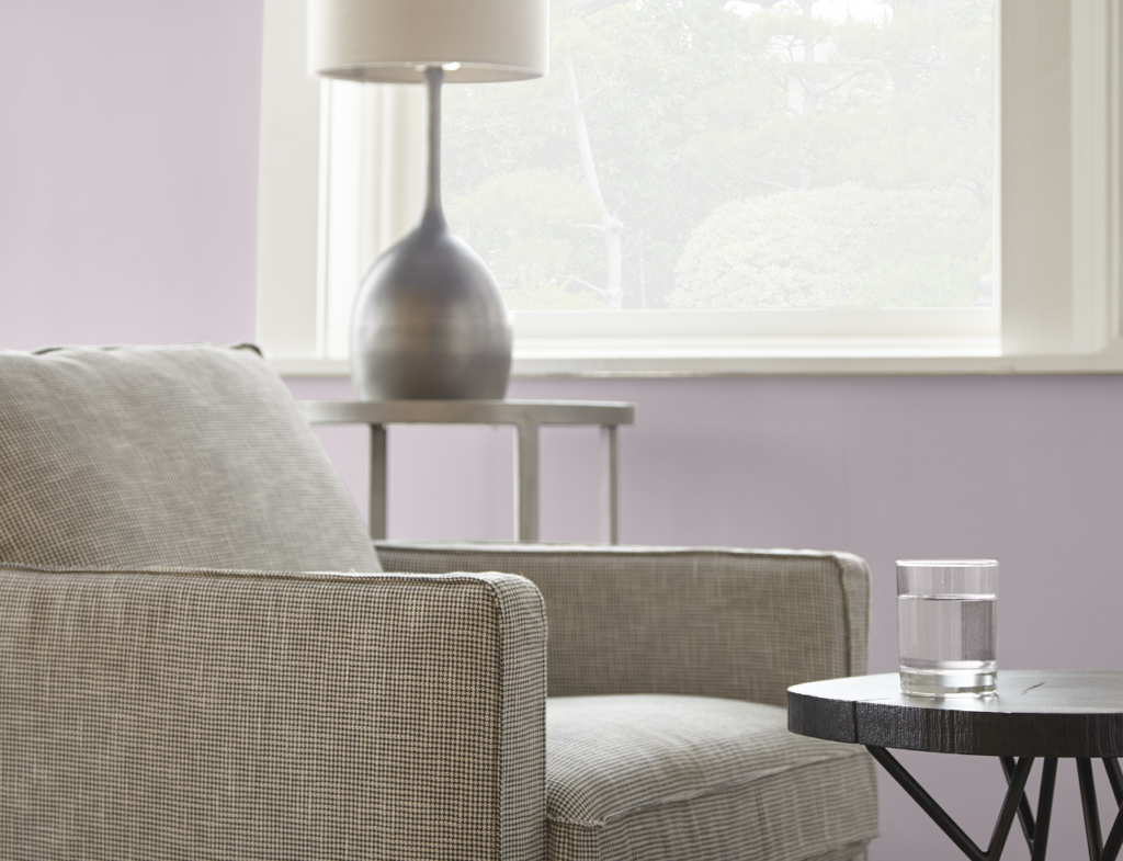 A closeup detail image of a living room, the room features neutral accent chair, a couple of accent table and a lamp.  The wall is painted in light purple color called Dusty Lilac.