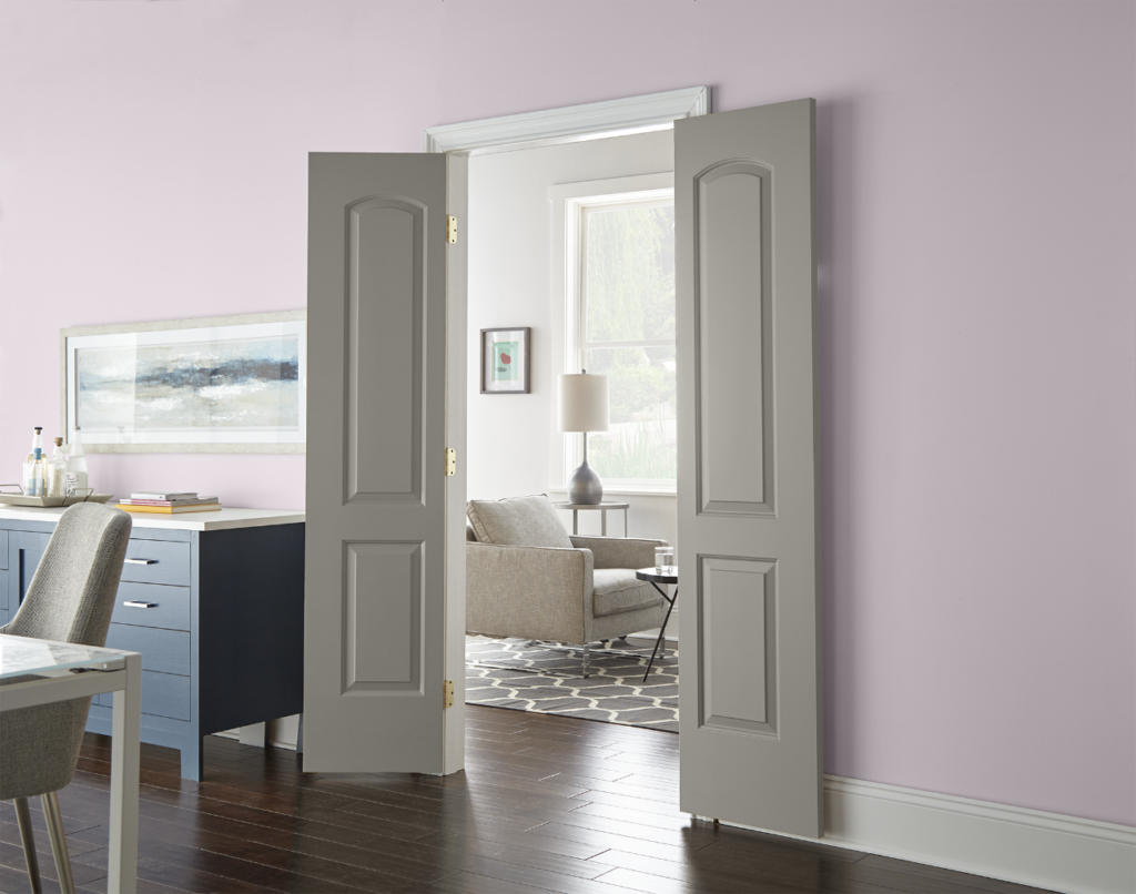 A room-to-room setting featuring casual modern furniture. There's a dining and living room area, dining room is painted with color called Dusty Lilac and the living area is painted with a white color called Painter's White. The wide two panel door that allows visibility from one room to the other is painted in khaki green, almost gray color called Battleship Gray.