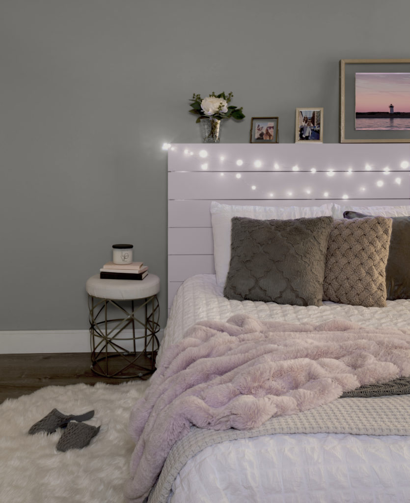 Bedroom featuring a wood plank headboard paint in Dusty Lilac. The bed has white bedding, with pink, gray and white blankets, and solid gray and brown pillows. Small lit twinkle lights wrapped around the headboard.