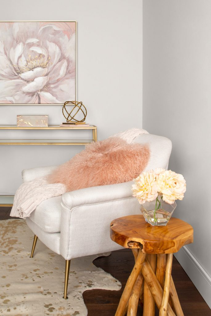 Side view of the sitting room with walls painted in Painter's White. White chair with gold legs and pink furry pillow. Natural Wood side table. Sofa table with gold trim and glass top.