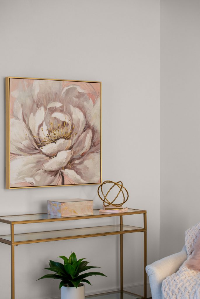 Close up of sofa table with gold trim and glass top sitting against wall painted in Painter's White. Large picture of a pink flower in a gold frame placed above table on the wall.