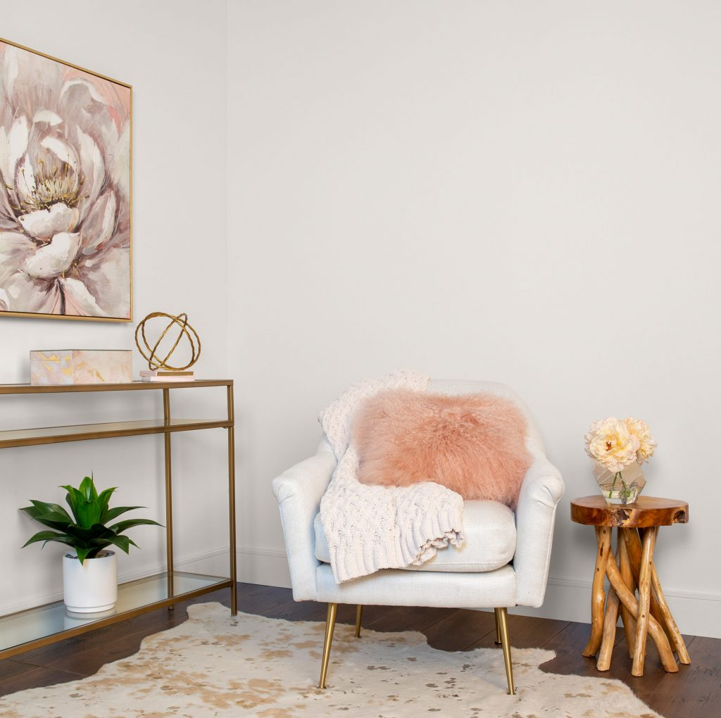 Front view of the sitting room with walls painted in Painter's White. White chair with gold legs and pink furry pillow. Natural Wood side table. Sofa table with gold trim and glass top.