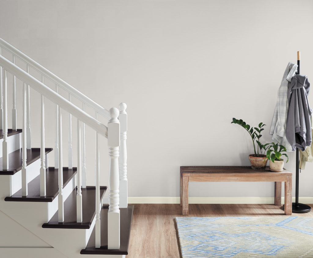 A simple hallway-stair case, the room is painted in white color called Painter's White.  The trim is features and even lighted, brighter white called Ultra Pure White. There is very minimal furniture and décor, only a sitting bench and coat rack.