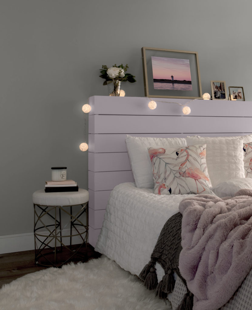 A side angle of a bedroom featuring a wood plank headboard paint in Dusty Lilac. The bed has white bedding, with pink, gray and white blankets, and flamingo pillows. Large lit rose ball lights wrapped around the headboard.