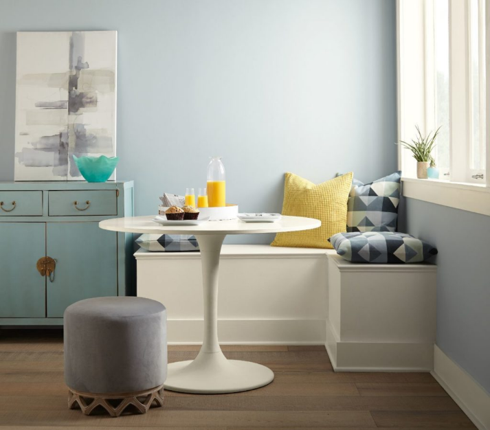 A breakfast nook decorated with casual and modern furniture.  The walls are painted in light color called Light Drizzle. The overall room is accented by a pop of yellow and teal.