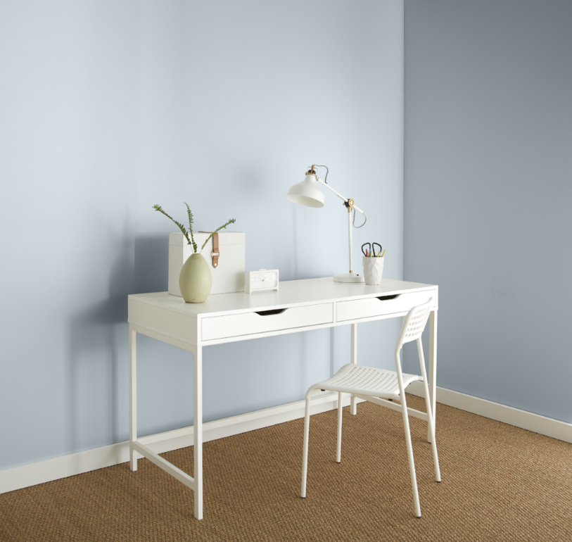 A casual home office area with all white desk and chair. The decor is very clean and minimal looking.  The walls are painted in a light blue color called Light Drizzle.