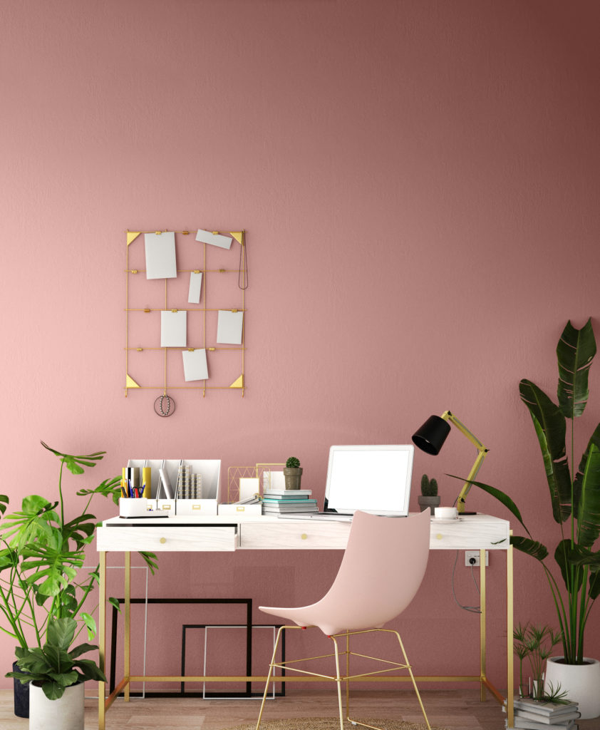 A home office with wall painted in light pink color. A desk with metallic gold hardware, items on the desk include laptop, a modern lamp, notebooks and potted plants.  Tropical potted plants create a calming atmosphere on this home office.