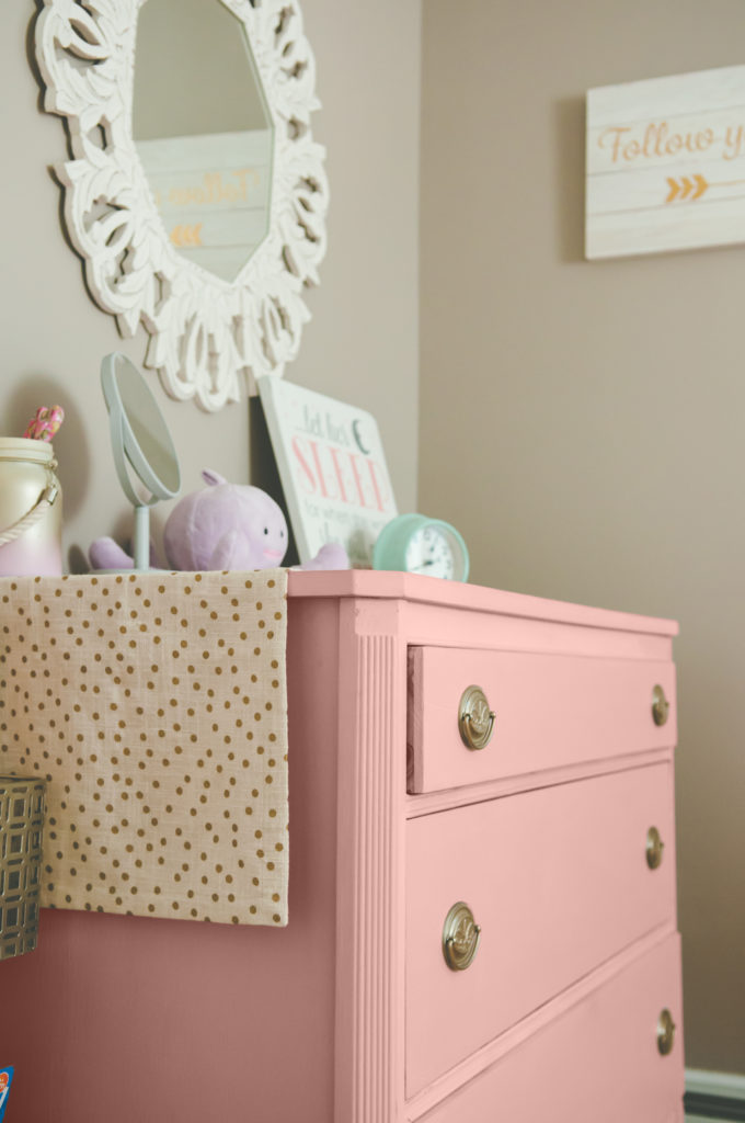 Pink dresser in baby nursery, items on dresser and mirror hanging on wall