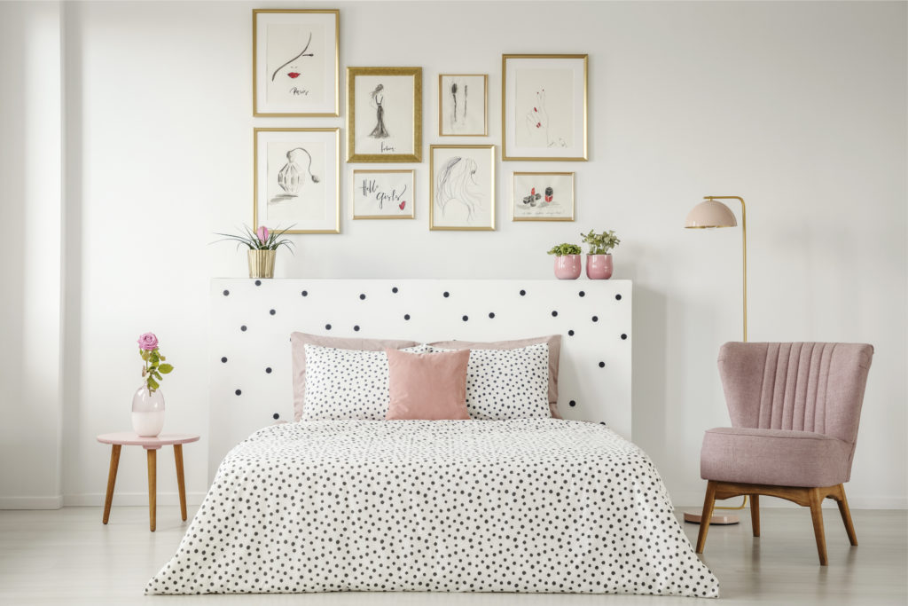 A bedroom interior with a double bed with dotted sheets, pink pillows and armchair, art collection and plants.