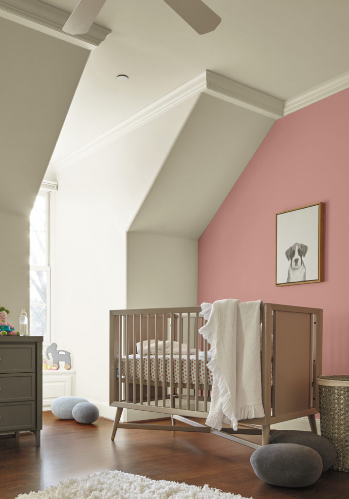 A nursery with natural light wood crib, accent wall painted in light pink color called Bubble Shell.