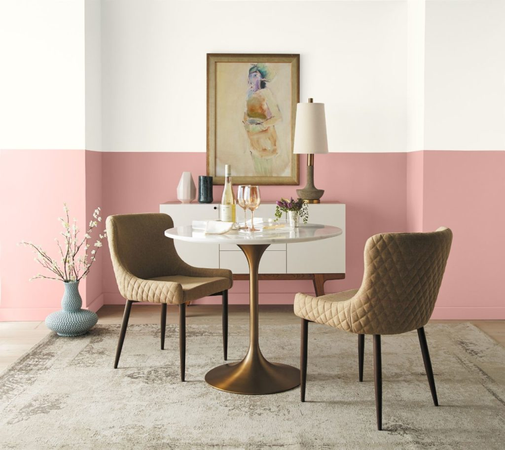 A two tone retro dining room. White upper wall and light pink lower wall.