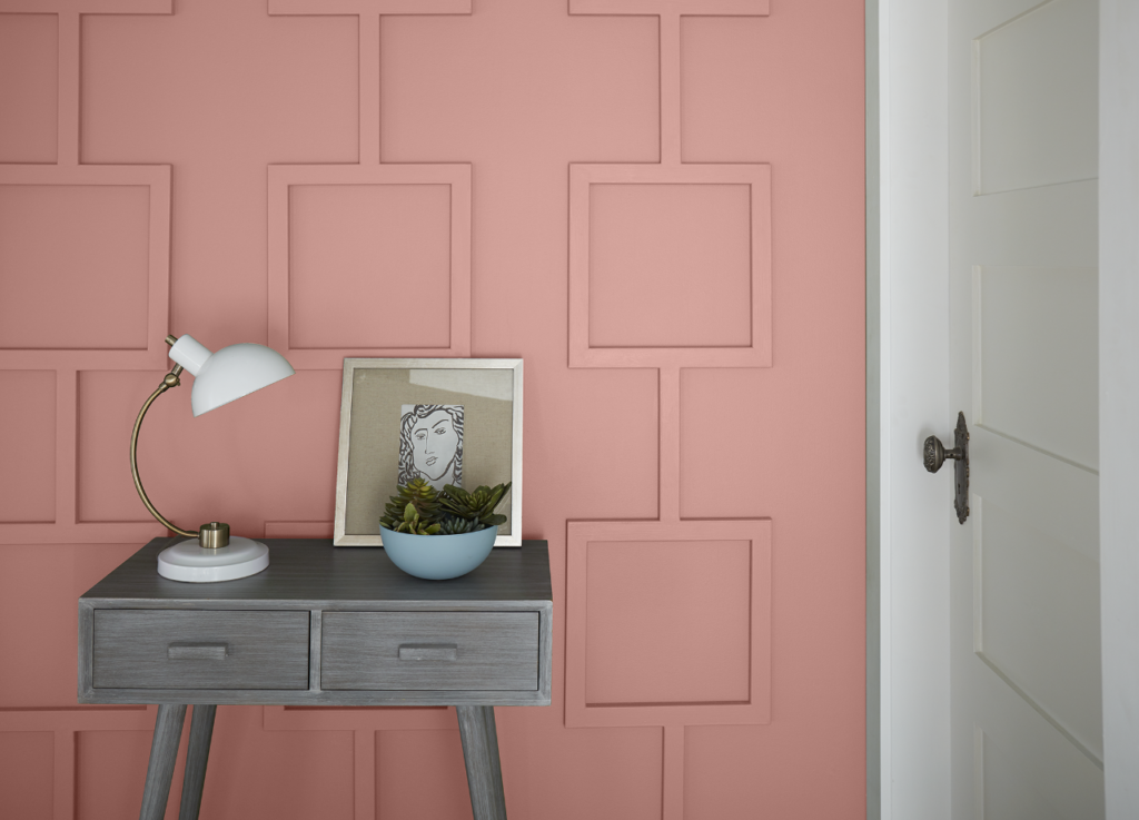 A geometric panel wall painted in light pink color. A decorative table with lamp ceramic bowl with succulent plant and a small frame leaning on the wall.