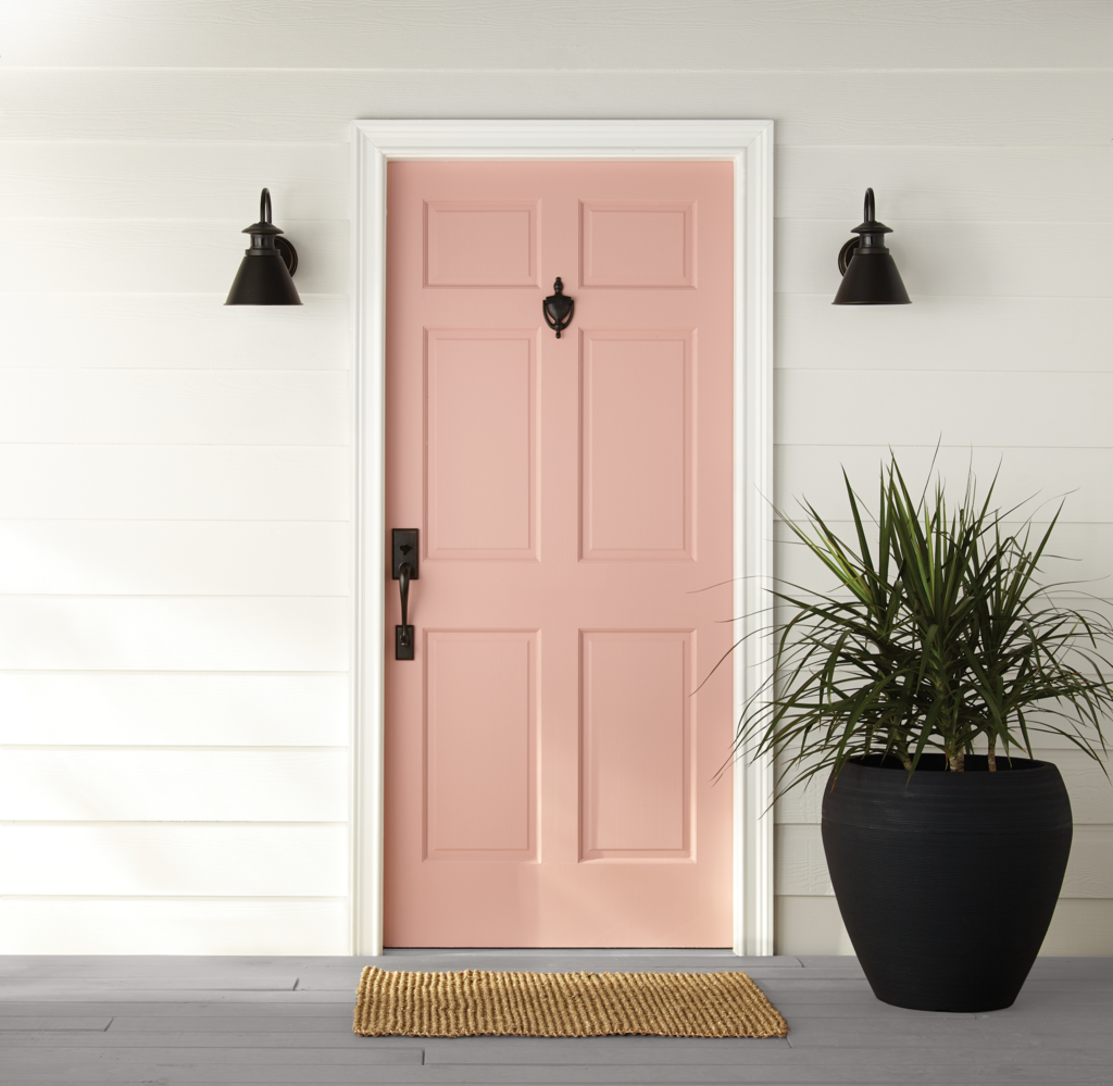 A main front door painted in light pink color called Bubble Shell.
