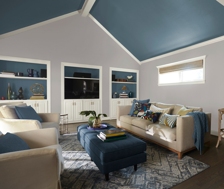This image shows a vaulted accent ceiling in Blueprint. It is a living room with sofas embellished with pillows and a blanket.  There is a long blue ottoman in between the sofas.              Also against the back wall is a built in wall unit also painted in Blueprint as an accent.