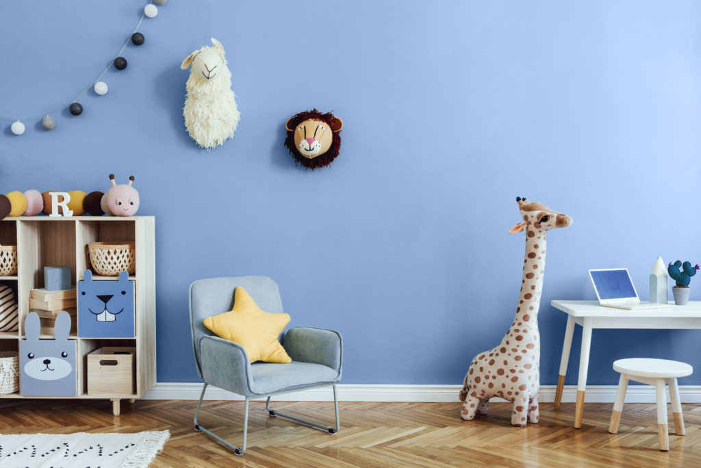 A blue Scandinavian nursery-playroom with wooden cabinet, desk, mint color armchair, baby accessories and toys.