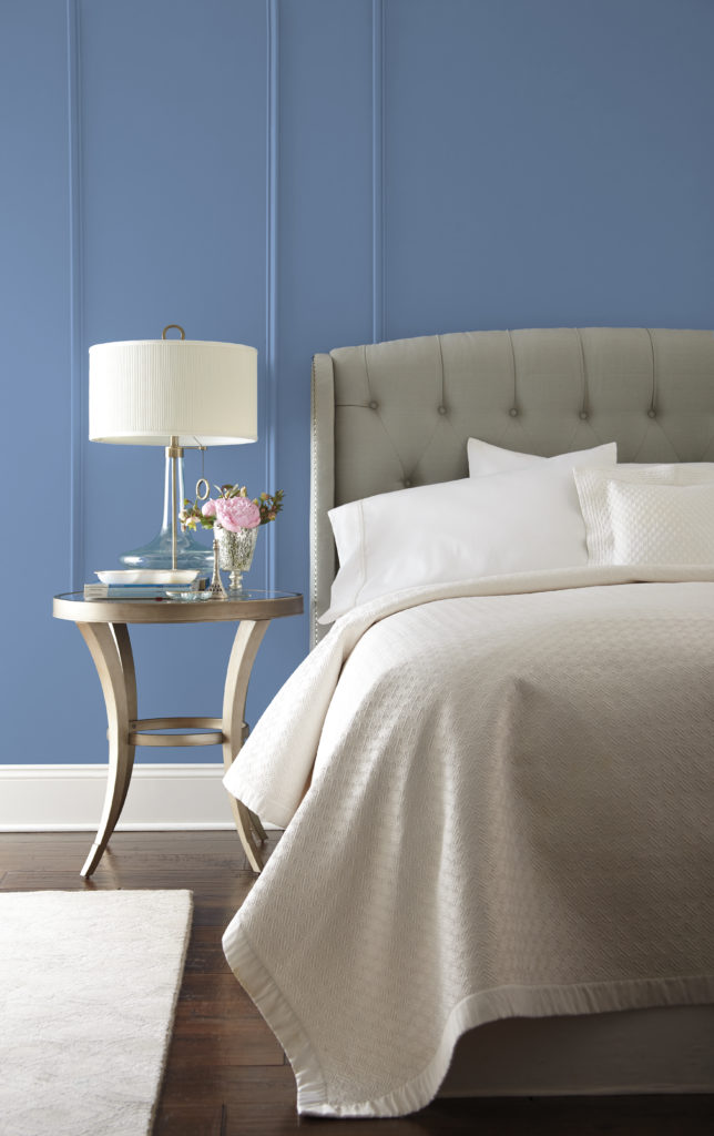 A chic blue bedroom with light gray upholstered bed headboard and dark hardwood floor which creates a sense of serenity and balance.