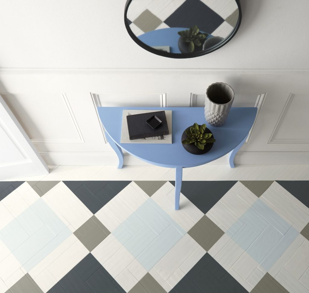 A blue half-moon console table and a geometric design on the floor created by using multiple colors including Bluebird paint color.