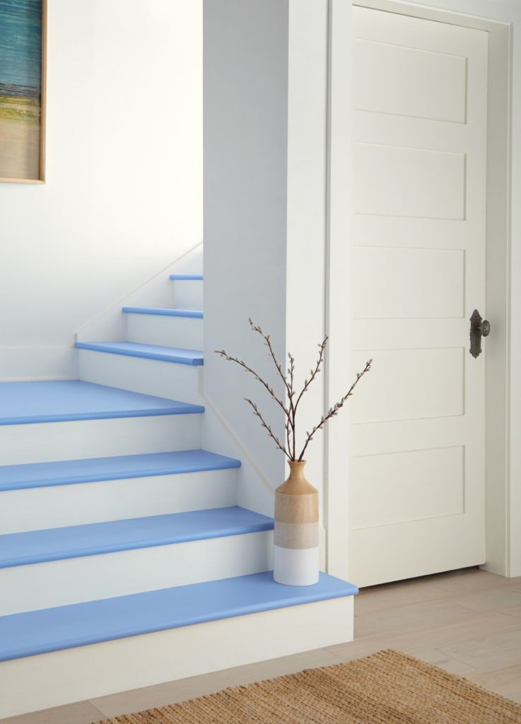 A staircase painted in mostly white paint, but steps are painted in a playful periwinkle blue color blue which adds character and draws your attention to each step.