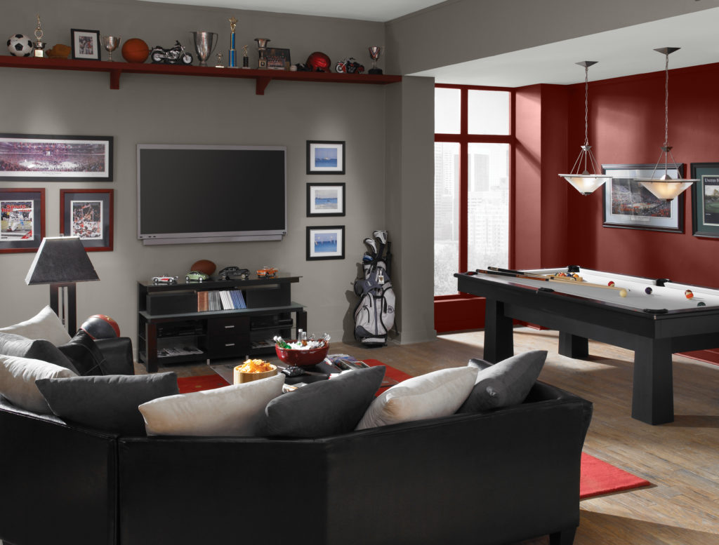 A living room with a couch and a lot of pillows. There is a large screen TV and a shelf with trophies on it mounted to a wall that is painted in a gray color. Across from this area is a smaller area with a pool table and walls painted in a red color.