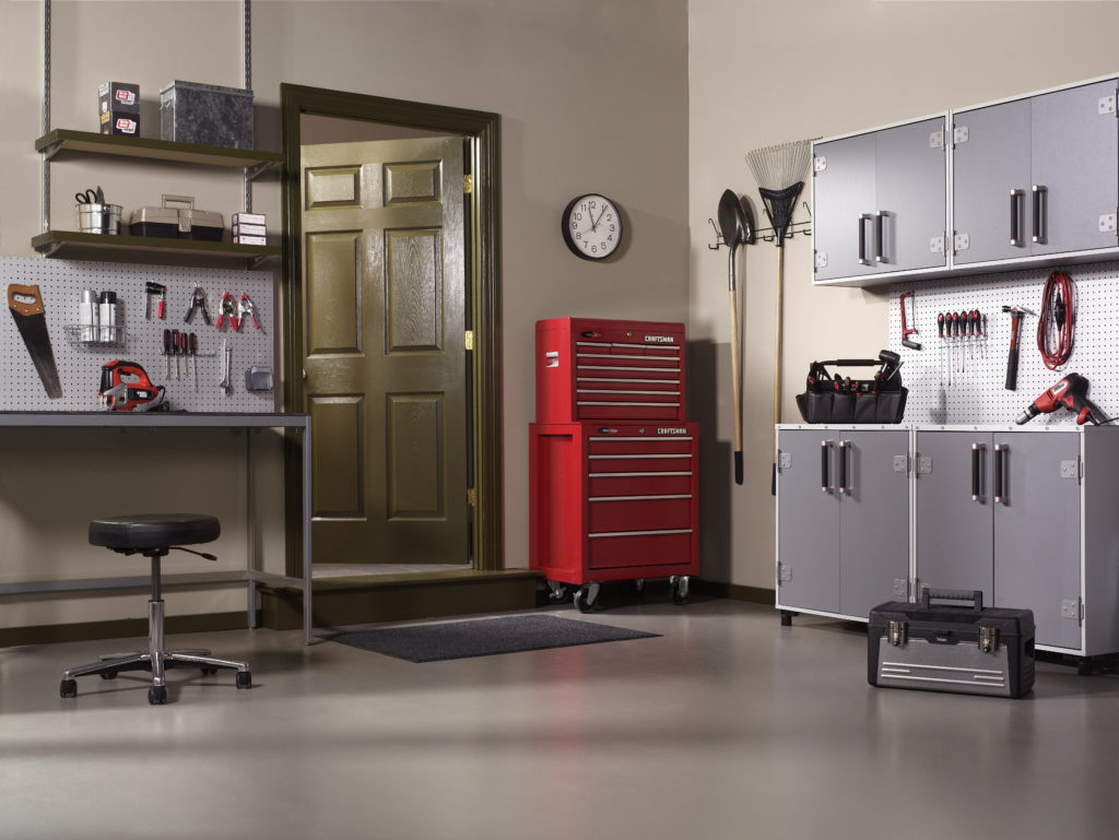 A garage that has been converted into a tool room with metal cabinets and a workbench.