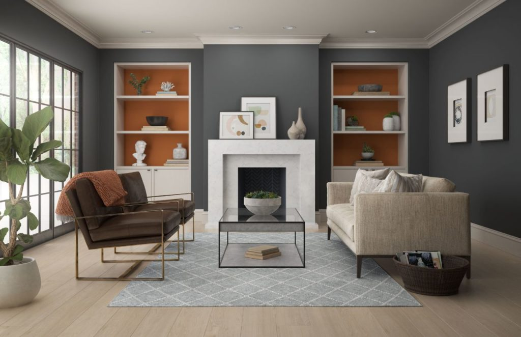A modern living room featuring white walls dark gray color. The room is accented with an orange paint color called Rumba Orange. The overall feel of the room is modern yet cozy and welcoming.