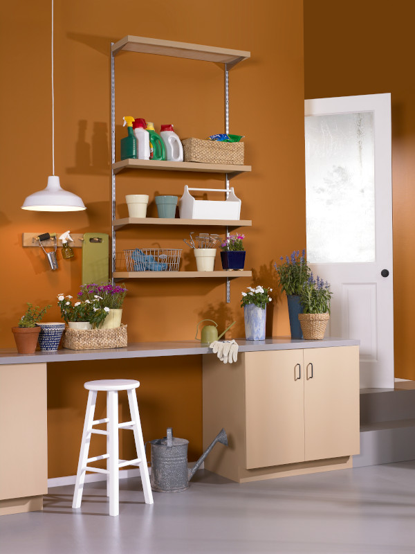 The interior of a garage with organization shelves and potting bench. Wall are painted in orange color called Rumba Orange.