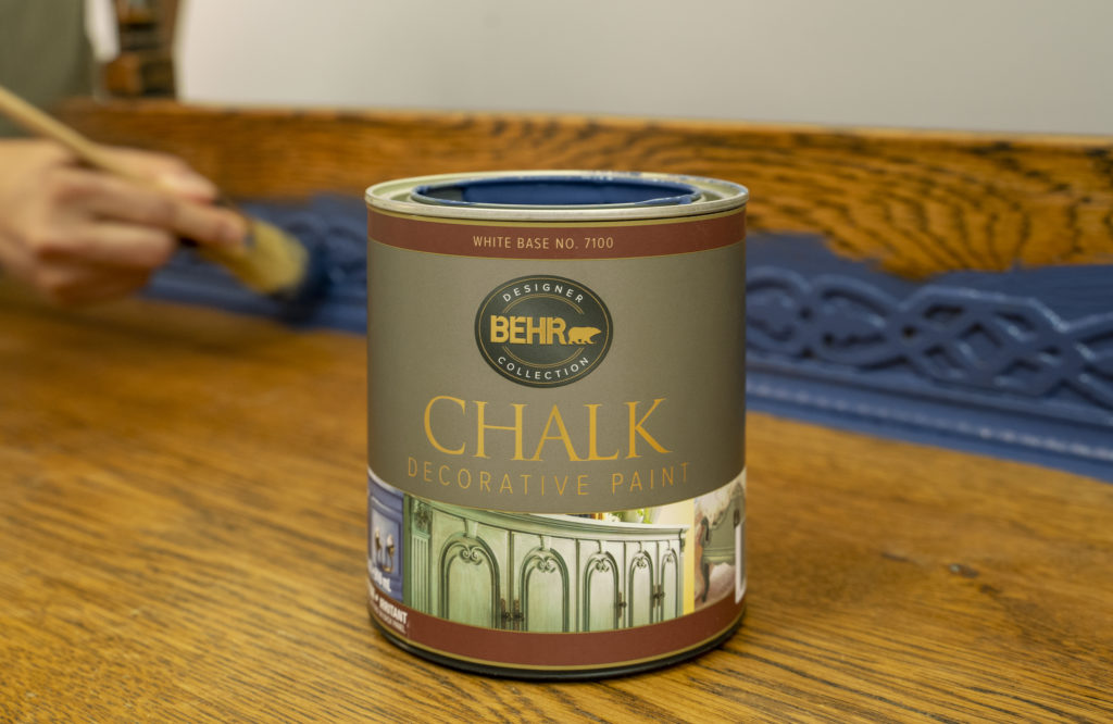 A BEHR decorative chalk paint sitting on top of a dresser and man's hands applying paint on the background.