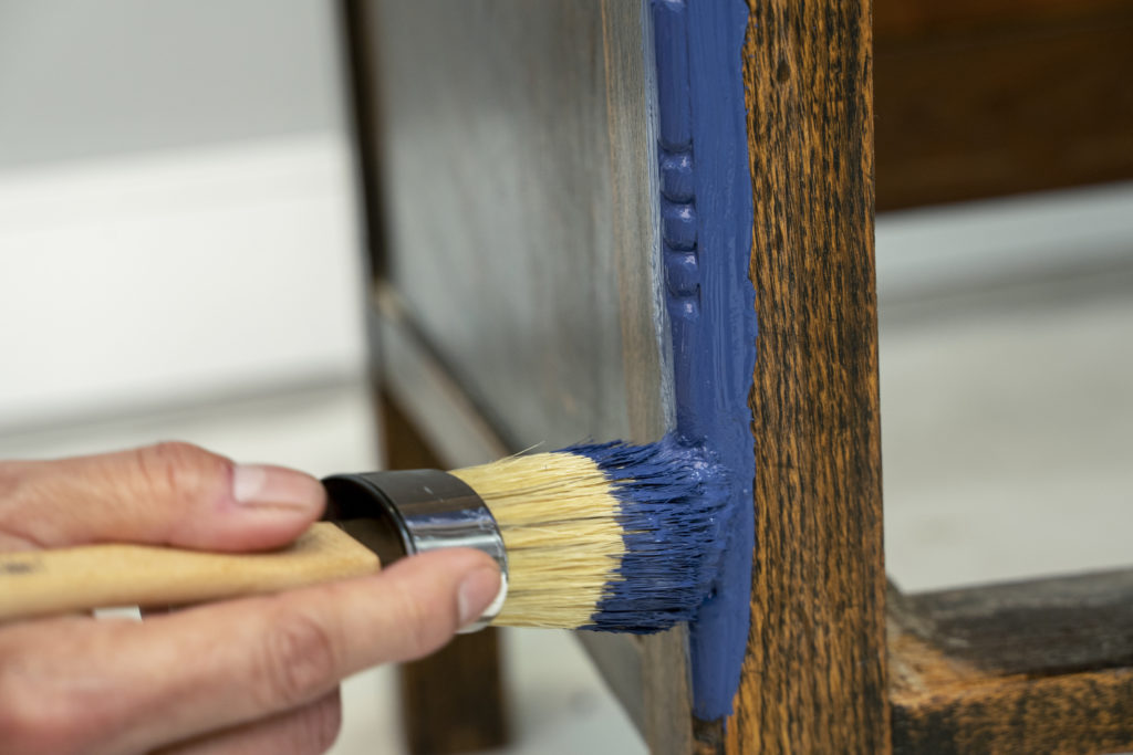 A closeup detail image of a hand holding a brush and painting a small furniture area.
