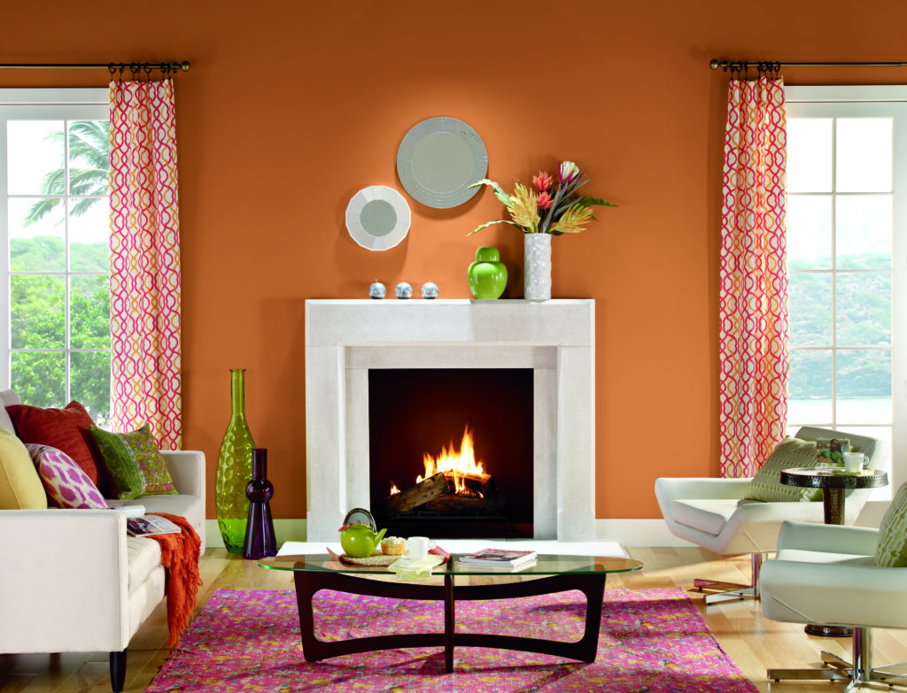 A modern-tropical style living room, wall is painted in orange color called Rumba Orange.