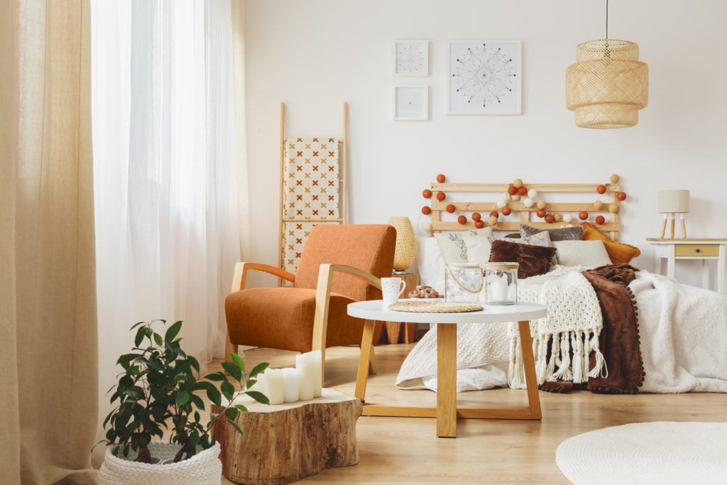 A cozy bedroom interior with comfortable orange chair facing the windows standing next to a wooden small table.