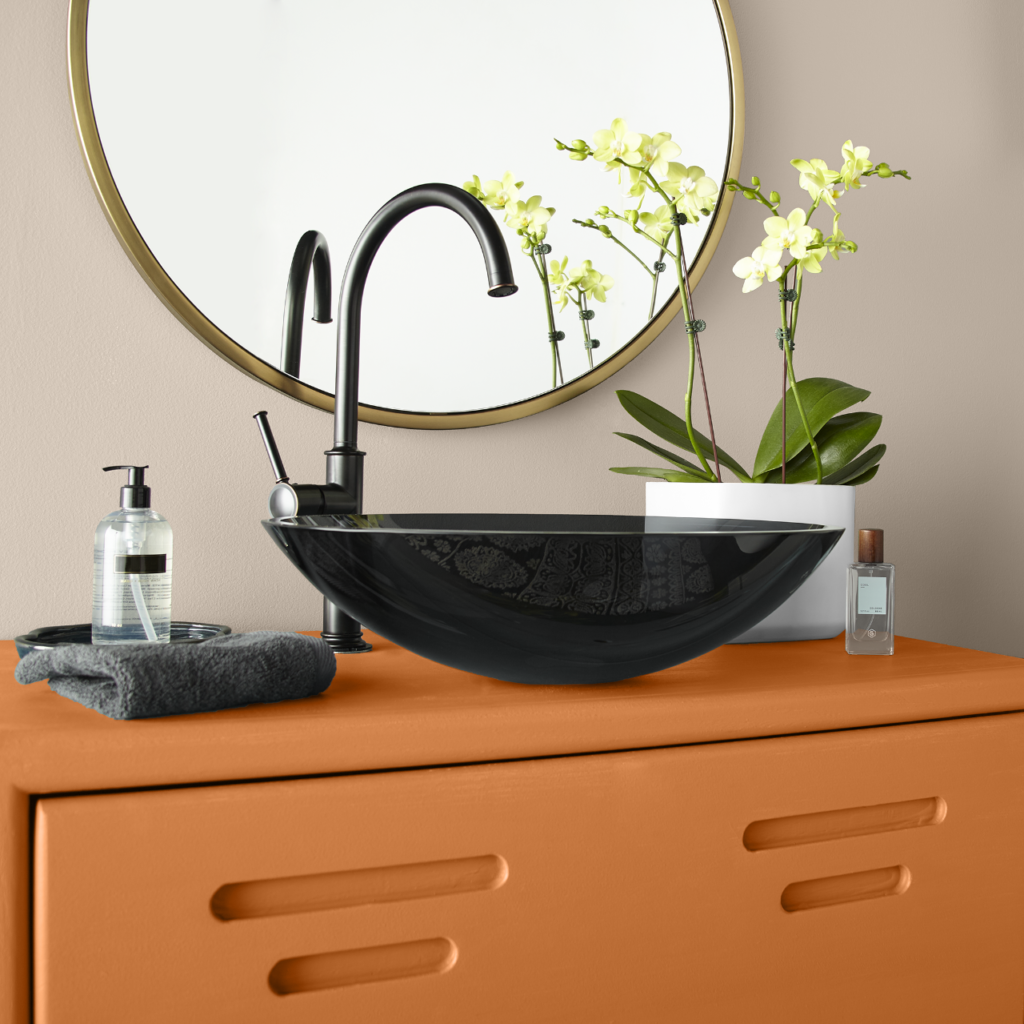 A closeup detail of a bathroom cabinet and sink. The metal cabinet is painted in orange color called Rumba Orange.