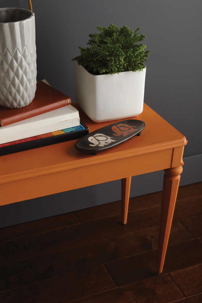 A gray wall and side orange side table.