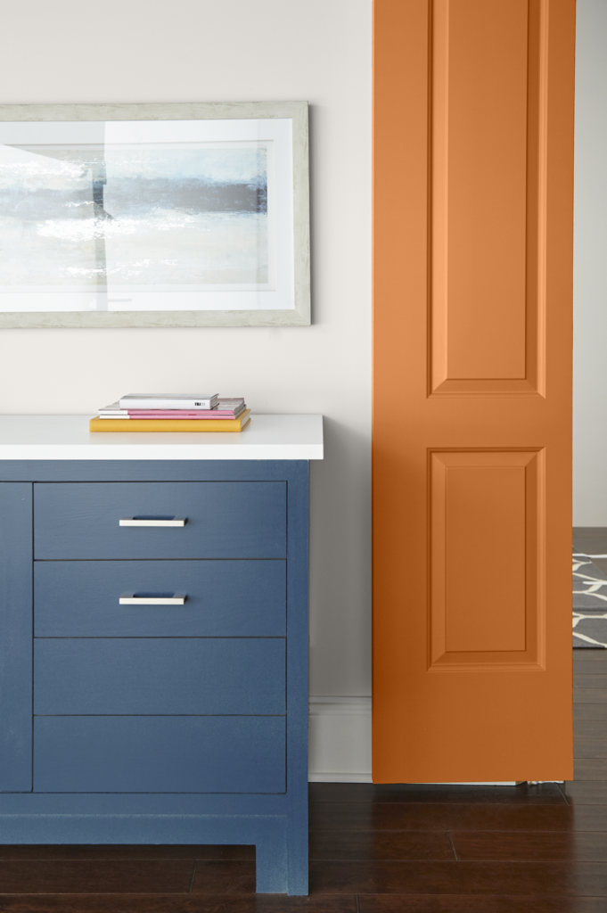 Hallway closeup and a single panel door painted in orange color called Rumba Orange.