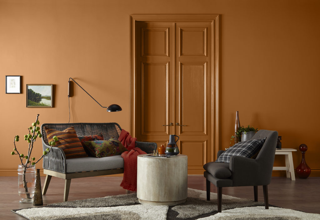 A global inspired sitting area painted with orange color called Rumba Orange. A mix of fabric colors and patterns used on upholstery.