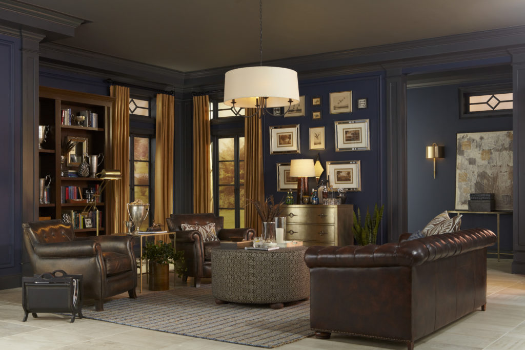 A living room with oversized leather chairs and couches. The walls are painted in a dark blue color.