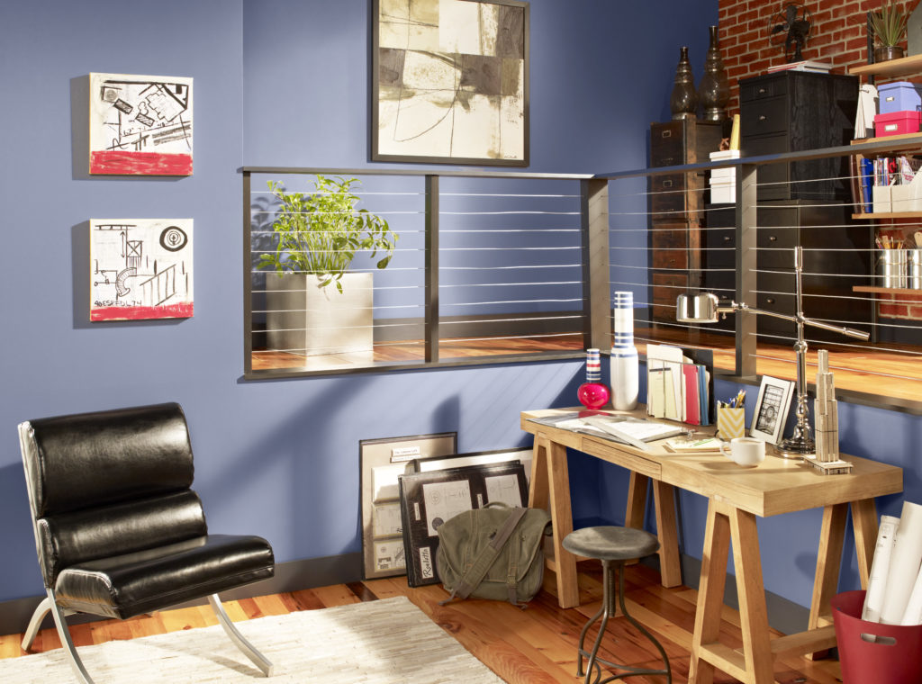 A home office with a small wood desk, stool and leather chair. The walls are painted in a blue color.