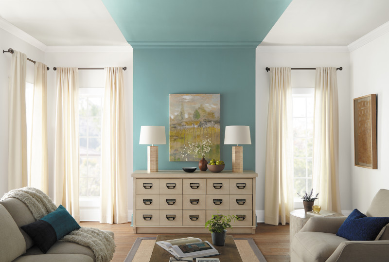 A well lit living room with a wall to ceiling accent painted in fresh blue-green  color called Dragonfly.
