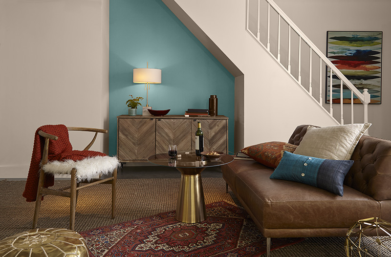 An interior living area featuring a staircase and nook below it, wall painted in blue color called Dragonfly. Several eclectic furniture and decorative elements featuring pops of blue, green and warm red tones.