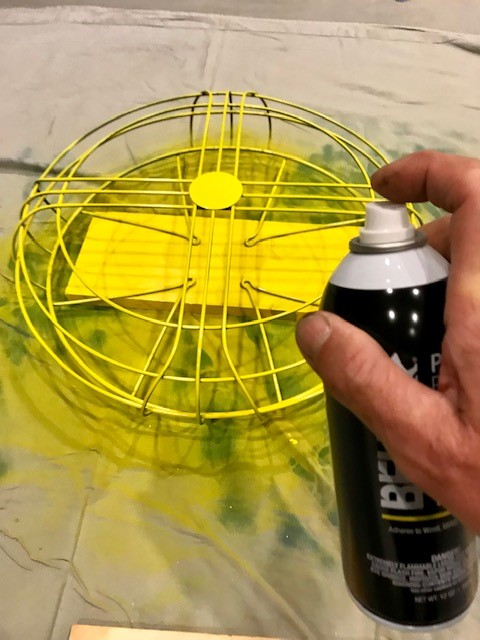 A man's hand spraying the fan guard with a bright yellow color called Unmellow Yellow.